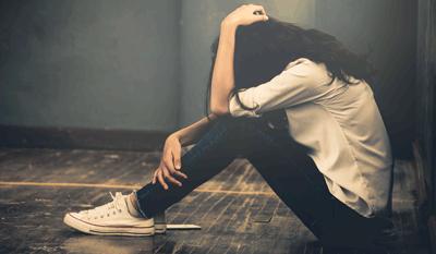 Depressive Frau in dunkelem Raum